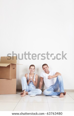 Attractive couple in a new apartment drinking tea