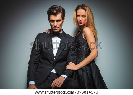 attractive couple in black posing in studio background looking at the camera. man is seated while woman stands by his side embracing him - stock photo