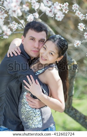 Attractive couple in blossoming park. Asian girl and european guy embracing among of blossoming almond branches - stock photo