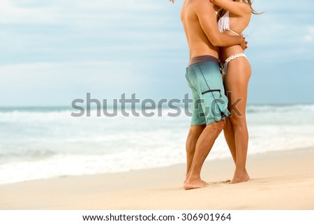 Attractive couple in embrace on sandy beach  - stock photo