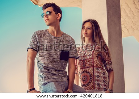 Attractive couple in sunglasses under blue sky. - stock photo