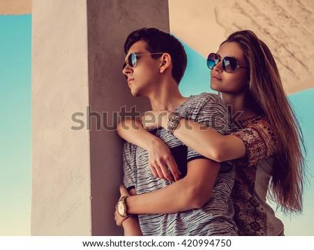 Attractive couple in sunglasses under blue sky. - stock photo