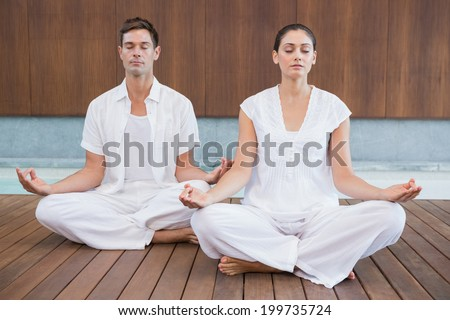 Attractive couple in white meditating in lotus pose in health spa - stock photo
