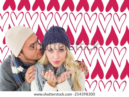 Attractive couple in winter fashion against valentines day pattern - stock photo