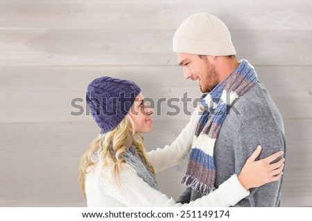 Attractive couple in winter fashion hugging against bleached wooden planks background - stock photo