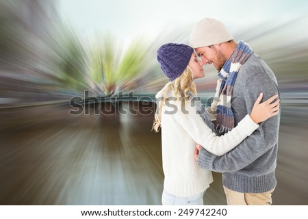 Attractive couple in winter fashion hugging against canal in amsterdam - stock photo