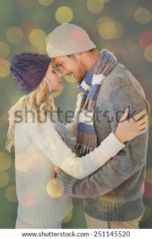 Attractive couple in winter fashion hugging against close up of christmas lights - stock photo