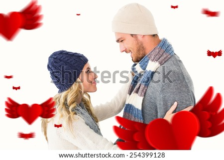 Attractive couple in winter fashion hugging against hearts - stock photo