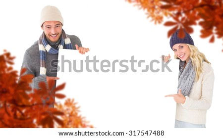 Attractive couple in winter fashion showing poster against autumn leaves - stock photo