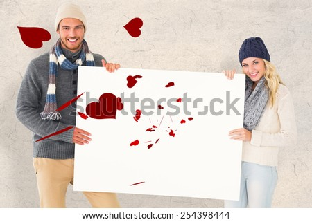 Attractive couple in winter fashion showing poster against parchment - stock photo