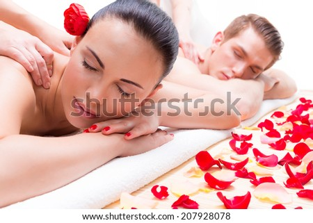 Attractive couple lying  in a spa salon enjoying a deep tissue back massage together. - stock photo
