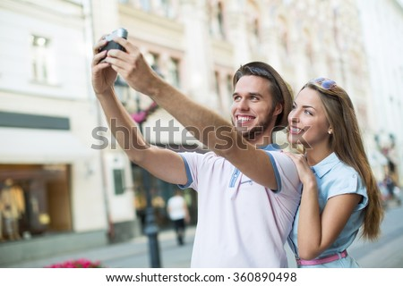 Attractive couple making selfie outdoors - stock photo