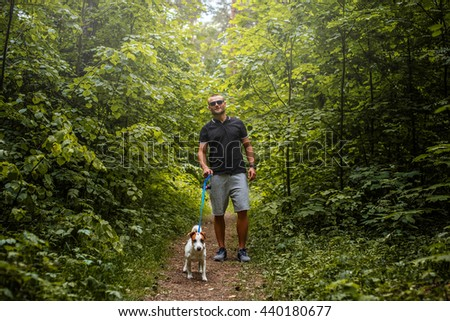 Attractive couple on a walk with a dog in a wood.