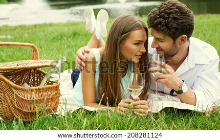 Attractive couple on picnic drinking white wine - stock photo