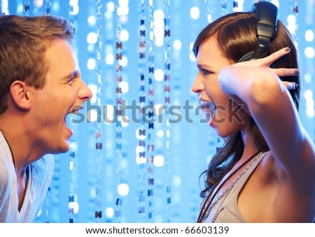 Attractive couple screaming in the nightclub - stock photo