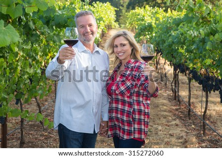 Attractive couple showing affection while holding wine glasses in a vineyard