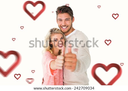 Attractive couple showing thumbs up to camera against hearts - stock photo