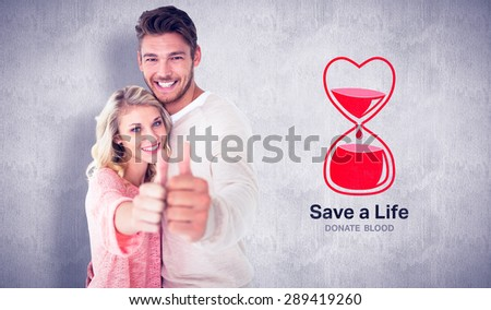 Attractive couple showing thumbs up to camera against white and grey background - stock photo