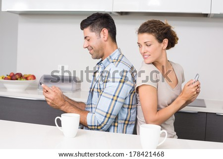 Attractive couple sitting back to back texting at home in kitchen - stock photo