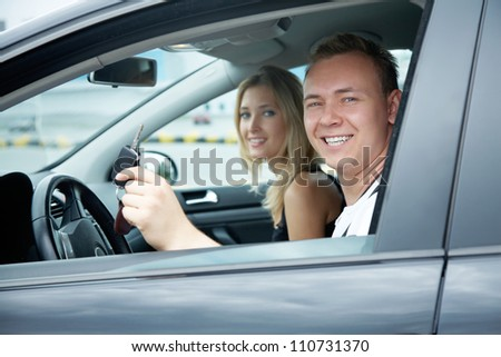 Attractive couple sitting in the car for test drive - stock photo
