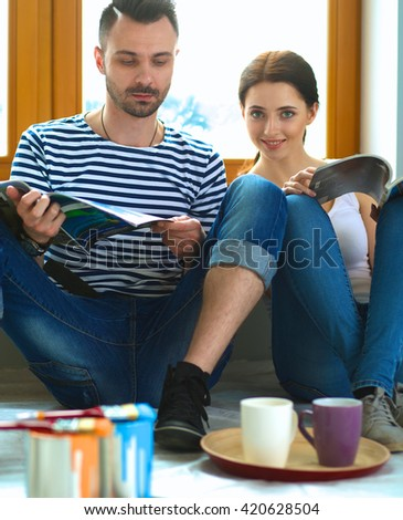 Attractive couple sitting on home floor looking at jurnal and smiling at each other. - stock photo