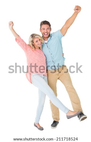 Attractive couple smiling and cheering on white background - stock photo