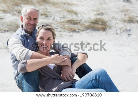Attractive couple smiling at camera on the beach on a bright but cool day - stock photo