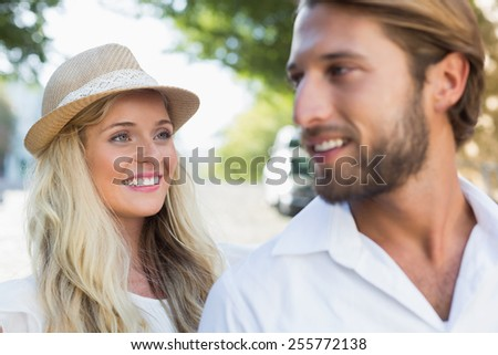 Attractive couple smiling at each other on a sunny day in the city - stock photo
