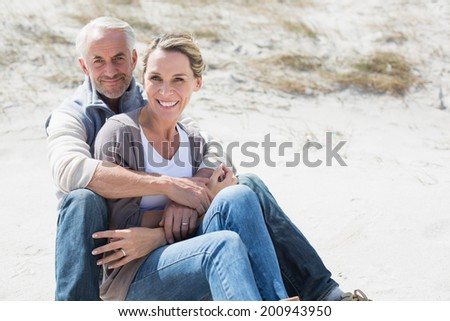 Attractive couple smiling at each other on the beach on a bright but cool day - stock photo