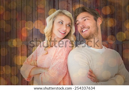 Attractive couple smiling with arms crossed against close up of christmas lights - stock photo