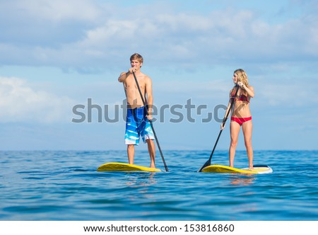 Attractive Couple Stand Up Paddling in Hawaii, Active Life Concept - stock photo