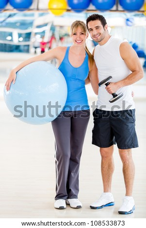 Attractive couple standing at the gym smiling