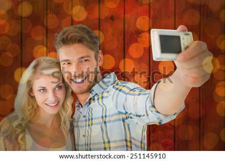 Attractive couple taking a selfie together against close up of christmas lights - stock photo