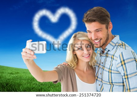 Attractive couple taking a selfie together against green field under blue sky - stock photo