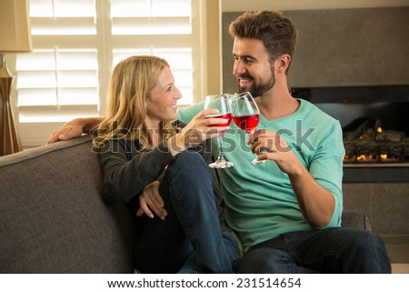 Attractive couple toasting with wine at home - stock photo