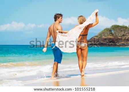 Attractive Couple Walking on Beautiful Beach - stock photo
