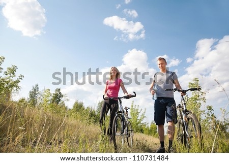 Attractive couple walking with their cycles after biking - stock photo
