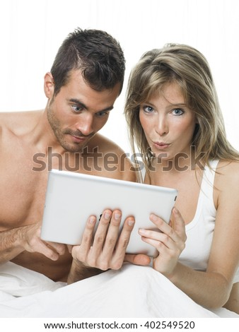 attractive couple watching things in a tablet - stock photo