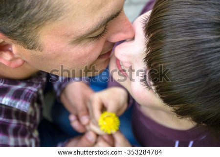 attractive couple with golden ring on dandelion arms holding together looking to each other kissing - stock photo