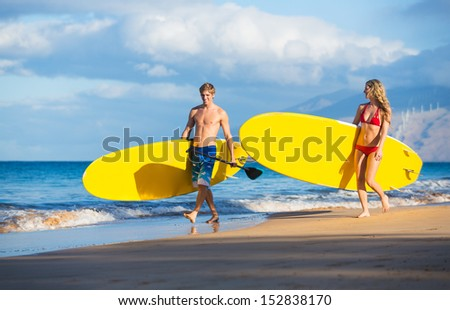 Attractive Couple with Stand Up Paddle Boards, SUP, on the beach in Hawaii - stock photo