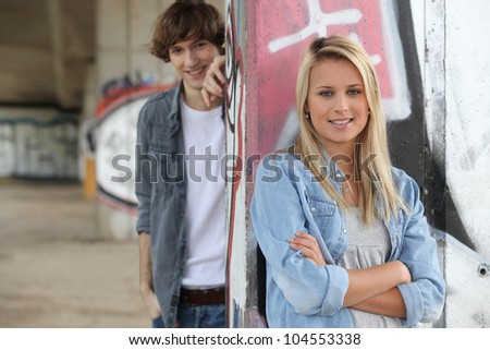 Attractive couples stood by graffiti covered wall - stock photo