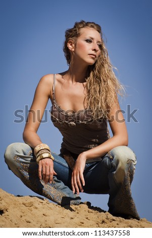 Attractive cowgirl in jeans on a sandy background - stock photo