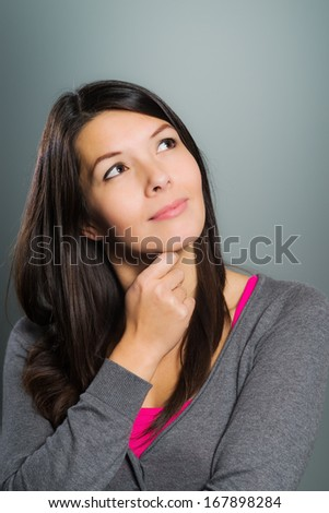 Attractive creative woman using her imagination sitting in deep thought with her hand to her chin looking up into the air with a contented smile as she dreams up innovative ideas