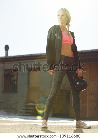 Attractive crossfit woman in sportswear holding a kettlebell outdoors - stock photo