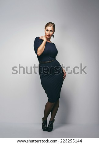 Attractive curvy woman in black dress looking away over grey background.  - stock photo