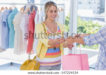 Attractive customer receiving her credit card and shopping bags - stock photo