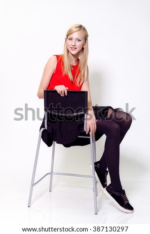 Attractive cute blonde on a chair on a white background