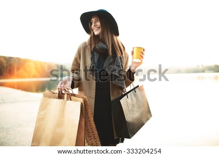 Attractive cute girl in with the shopping bags and warm drink in her hand - stock photo