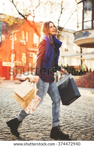 Attractive cute girl in with the shopping bags in her hand in the street on a sunny day at sunset - stock photo