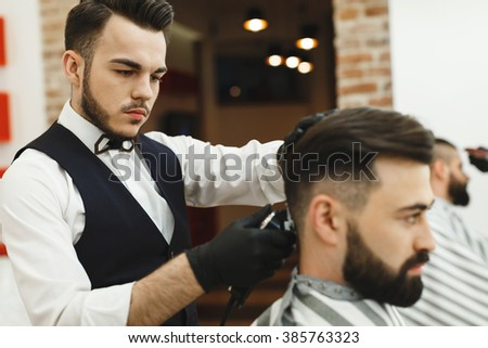 Attractive dark haired man wearing white shirt doing a haircut for man with black hair at barber shop, copy space, close up.